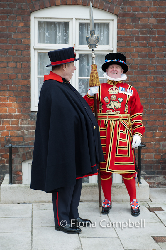 Yeoman Warder (left) wearing the navy blue and red undress uniform.