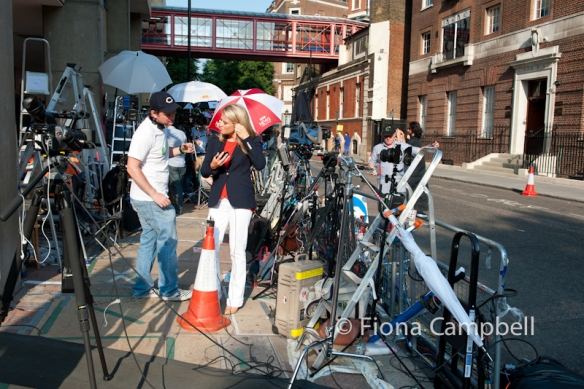 TV presenter adjusts her earpiece outside the Lindo Wing the day before the birth...